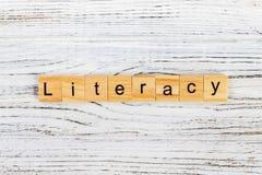 Слово ГРАМОТНОСТИ сделанное с деревянной концепцией блоков стоковые изображения