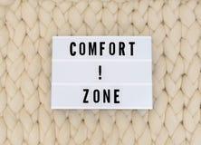 Слово ЗОНЫ КОМФОРТА на lightbox на предпосылке knit Концепция зоны комфорта стоковая фотография
