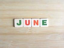 Слово июнь на деревянной предпосылке стоковые изображения rf