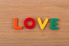 Слово ЛЮБОВЬ положено вне от покрашенных пластиковых писем стоковое изображение