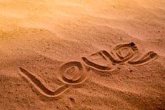 Слово ЛЮБОВ писать на песке природы на пляже отключение лета стоковое изображение