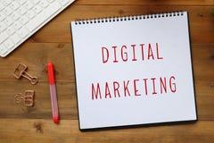 Слово маркетинга цифров на бумажной предпосылке тетради Стоковое фото RF