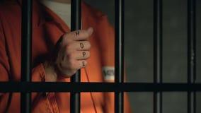 Слово надежды на заключенных в тюрьму пальцах человека, держа бары тюрьмы, мечта о свободе сток-видео