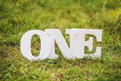 Слово одно на траве как оформление стоковые фотографии rf