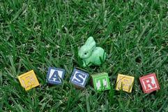 Слово пасха показанная на траве с figurine зайчика Стоковые Фотографии RF