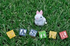 Слово пасха показанная на траве с figurine зайчика Стоковая Фотография RF