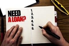 Слово, писать потребности вопрос о займа Концепция дела для ипотечного кредита написанного на книге, деревянная предпосылка с рук Стоковая Фотография RF