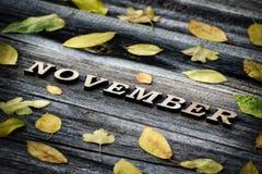 Слово письма -го ноябрь, деревянные Рамка желтых листьев, деревянная предпосылка Стоковое Фото