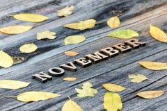 Слово письма -го ноябрь, деревянные Рамка желтых листьев, деревянная предпосылка Стоковое фото RF