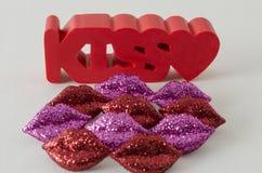 Слово поцелуя в красном цвете с маленьким сердцем и немногое shinny красные и пурпурные губы стоковые изображения rf