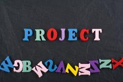 Слово ПРОЕКТА на черной предпосылке составленной от писем красочного блока алфавита abc деревянных, космосе доски экземпляра для  Стоковые Фотографии RF