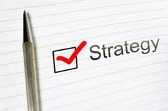 Слово стратегии написанное на выровнянной бумаге business concept images more my portfolio startegy Флажок и ручка стоковая фотография