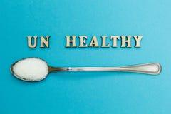 """Слово """"ООН здоровое """", ложка с сахаром на голубой предпосылке, концепцией стоковое изображение rf"""