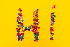 """Слово """"Hi """"от пестротканых круглых игрушек на желтой предпосылке стоковая фотография"""