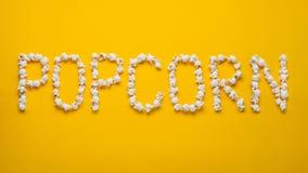 Слово POPKORN положено вне от частей попкорна соли на желтую предпосылку Взгляд сверху Плоское положение стоковая фотография