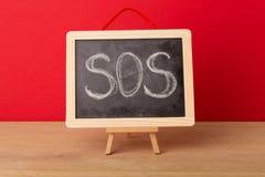 Слово Sos написанное на классн классном школы Стоковое Фото