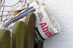 Сложенная газета зажатая между пикетчиками деревянной загородки Стоковые Изображения