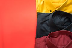 Сложенные мужские рубашки моды для взрослого собрания на красной предпосылке стоковые изображения