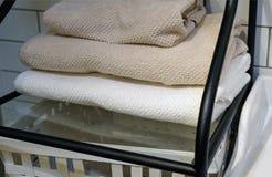 Сложенные полотенца, тапочки ковра и купальные халаты на полке шкафа в гостинице стоковое фото