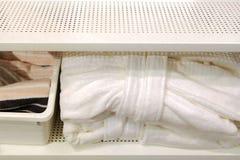 Сложенные полотенца, тапочки ковра и купальные халаты на полке шкафа в гостинице стоковое фото rf