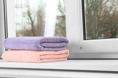 Сложенные чистые полотенца на силле окна стоковое фото