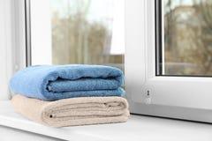 Сложенные чистые полотенца на силле окна стоковая фотография rf