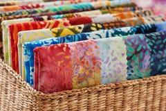 Сложенные яркие части выстегивая тканей батика в корзине, макрос Стоковое Фото