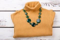 Сложенный желтый пуловер с зеленым ожерельем Стоковое фото RF