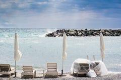 3 сложенных зонтики и стуль на пляже Стоковая Фотография RF