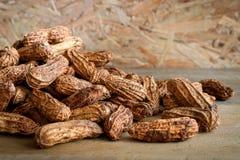 Сложите сырцовые арахисы в раковине на деревянной предпосылке Стоковая Фотография