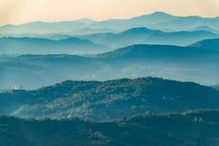 Слои гор в помохе во время захода солнца Красивый заход солнца в горах Красивый заход солнца в холмистой долине с деревнями стоковая фотография