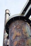 Слои подиумов вокруг огромных трубок наряду с дымовыми трубами, тяжелой ржавчиной и слезать патину краски стоковые фото
