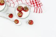 Слои югурта и клубники десерта в striped стекле на красной Стоковые Фото