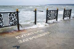 Сломанная загородка металла на обваловке моря во время сильного шторма и надпись на пристани - запрещено плавание, никакое swimmi стоковые изображения