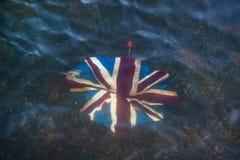 Сломанный зонтик с Юнионом Джек на ем, сброшенный в мелком реке стоковое фото