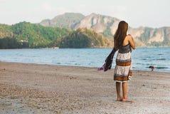 Сломленная сердечная женщина смотря волны дуя берег безвыходно стоковое изображение