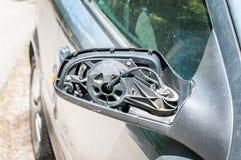 Сломленное и поврежденное бортовое зеркало заднего вида на серебряной автомобильной двери при остальные провода держа пластичную  Стоковые Изображения