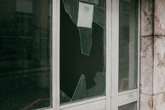 Сломленное окно в результате землетрясения или вандализма или другого отрицательного события стоковые фотографии rf