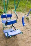 Сломленное пластичное качание ` s детей в спортивной площадке, покрашенный, сваривая на металле, для того НОП не сломать, старые  стоковые изображения