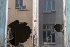 Сломленное стекло окна в покинутом старом здании Пакостный фасад Концепция разрушения Концепция вандализма Экстерьер архитектуры  стоковая фотография