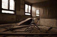 Сломленные мебели в получившемся отказ здании в грязной комнате стоковые фотографии rf