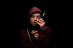 Сломленный и сиротливый спиртной человек с депрессией на черной предпосылке Мужчина с бутылкой полной напитка спирта стоковое фото rf