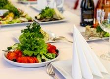 Служат блюда к таблице на праздник Столовый прибор и еда на белых скатертях в ресторане Конструируйте праздничное стоковое фото