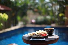 Служат завтрак бассейном на деревянном столе Стоковая Фотография RF