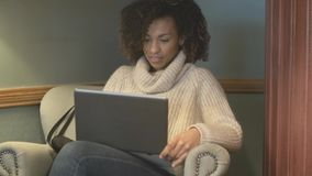 Случайная женщина студента сидя на кофейне и используя ноутбук видеоматериал