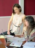 2 случайно одетых модели молодых дам сидят на столе в винтажном офисе и обсуждают модельные документы отпуска стоковое фото rf