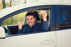 Случайные ключи автомобиля показа водителя парня из окна Успешный молодой человек купил новый автомобиль, держа кулак вверх по пл стоковое изображение