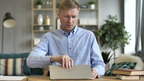 Случайный бизнесмен ноутбук приходя, сидеть и открытие на работе акции видеоматериалы