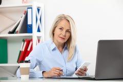 Слушать к требованиям к клиентов Красивая середина постарела женщина говоря на умном телефоне и усмехаясь на ее месте службы Стоковая Фотография