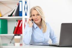 Слушать к требованиям к клиентов Красивая середина постарела женщина говоря на умном телефоне и усмехаясь на ее месте службы Стоковое Изображение